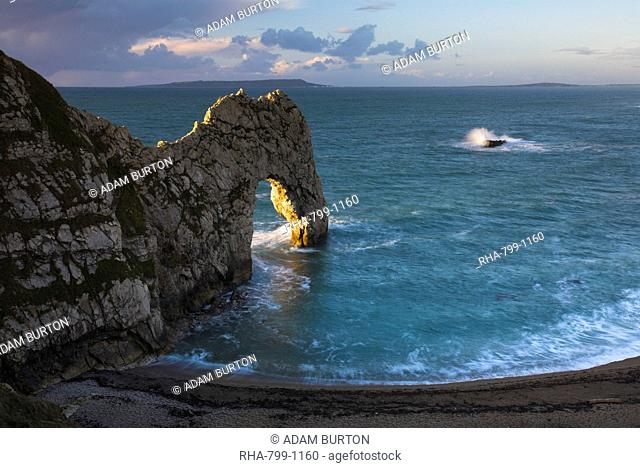 The archway of Durdle Door glows golden in early morning sunlight, Jurassic Coast, UNESCO World Heritage Site, Dorset, England, United Kingdom, Europe