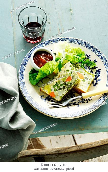 Plate of quiche with jam and lettuce