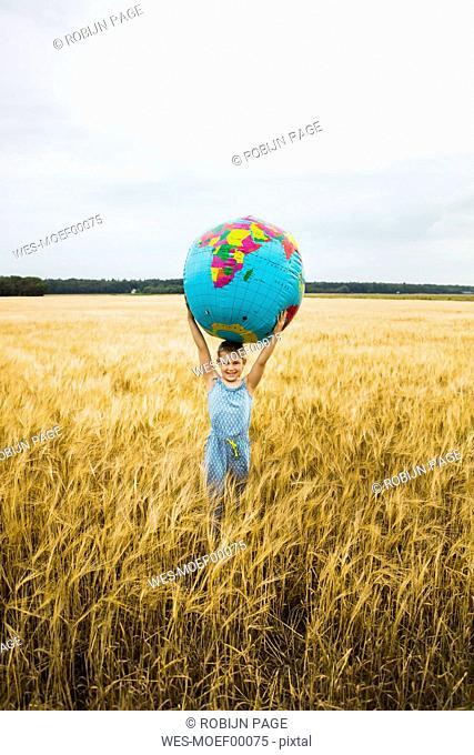 Girl standing in grain field holding globe