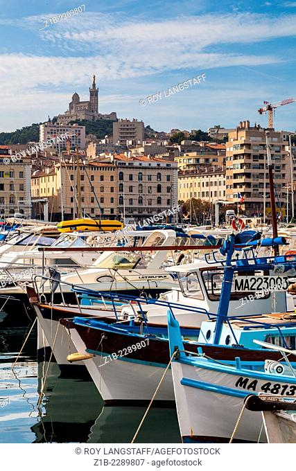 Fishing boats in the Old Port of Marseille with the Notre Dame de la Garde on the hill