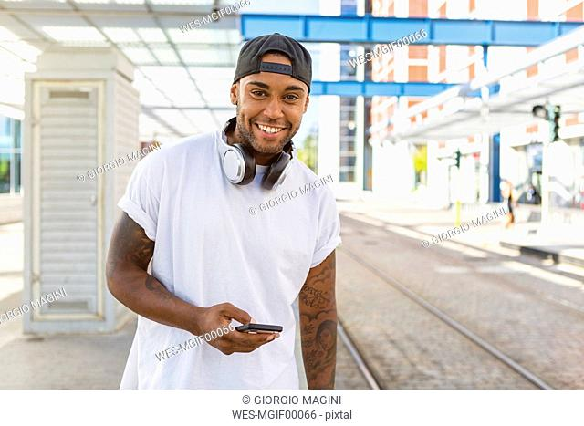 Portrait of smiling young man with headphones and smartphone waiting at tram stop
