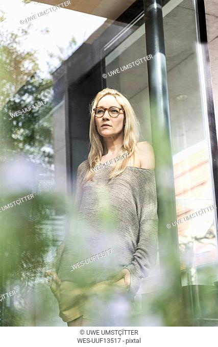 Portrait of blond mature woman standing on terrace