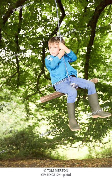 Boy in wellies swinging on tree rope swing