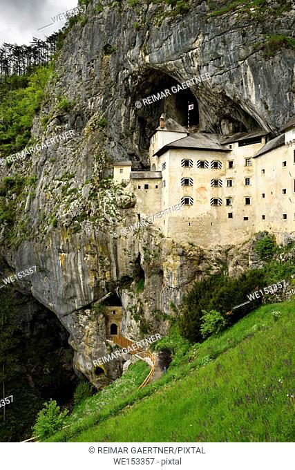 Grass hillside and cliff cave entrances at Predjama Castle 1570 Renaissance fortress built into the mouth of a cliffside cave in Slovenia