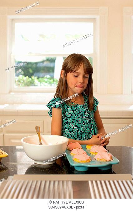 Young girl looking at cupcakes, licking lips