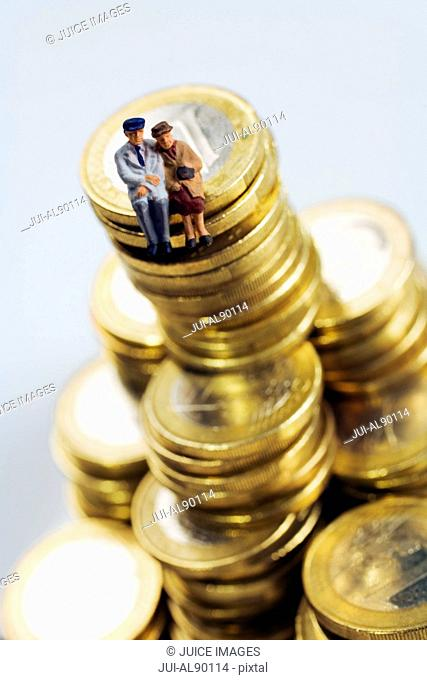 Senior couple figurines on stack of One Euro coins