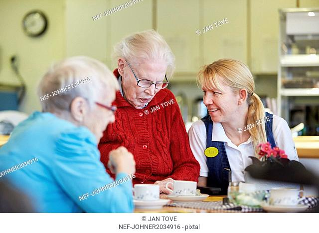 Nurse in care home talking with senior patients