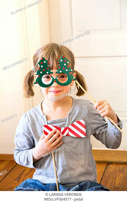 Portrait of smiling little girl with Christmas tree spectacles and toy bow