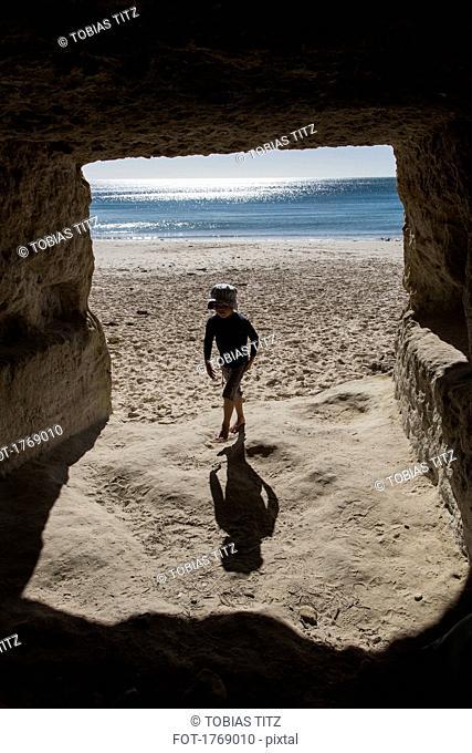 Boy on sunny ocean beach walking into cave