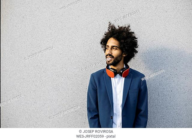 Smiling young businessman with headphones at a wall