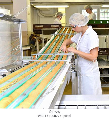Germany, Saxony-Anhalt, woman controlling cookies on production line in a baking factory