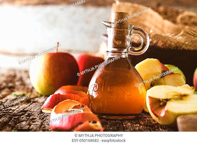 Apple vinegar. Bottle of apple organic vinegar on wooden background. Healthy organic food