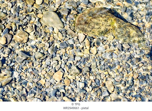 In the river, pebbles under water with reflecting light