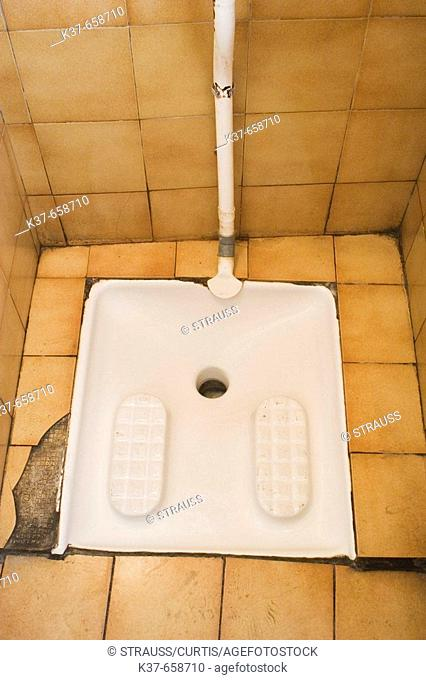 French squat toilet, used by squatting, rather than sitting