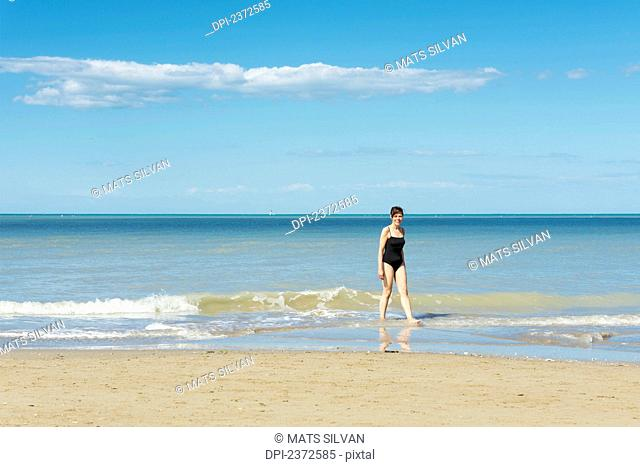 A Woman In A Bathing Suit Walks In The Shallow Water On The Beach; Rimini, Emilia-Romagna, Italy