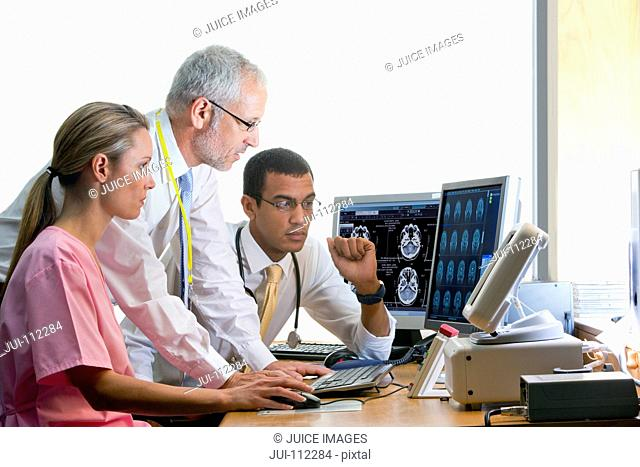 Doctors and nurse reviewing digital brain scan in doctor