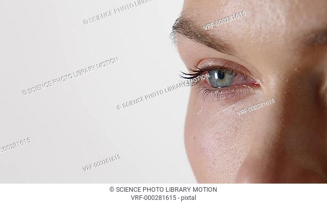 Close-up of a woman crying with a tear falling from her eye