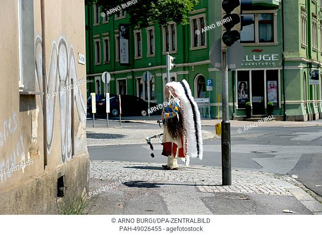 """A man dressed as Native American stands next to a traffic light in Radebeul, Germany, 31 May 2014. The Karl May Festival with the motto """"""""IndianSpirit"""""""" runs..."""