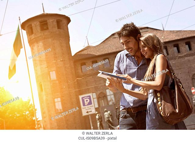 Young couple looking at guidebook, Turin, Piedmont, Italy