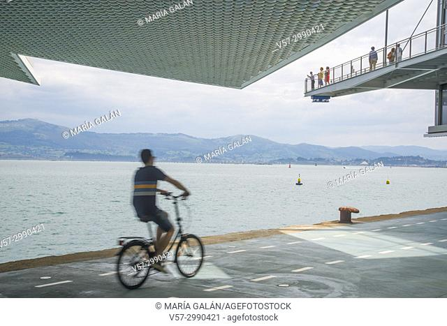Man riding a bike and view of the bay from Botin Center. Santander, Spain