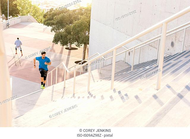 Man training, running up stairway at sport facility, downtown San Diego, California, USA