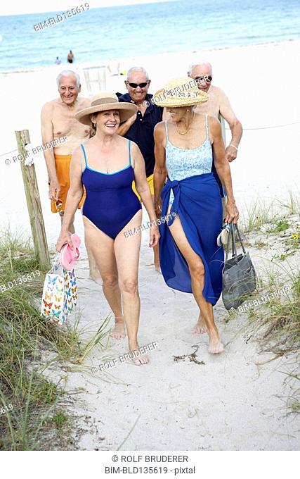 Senior friends walking on beach