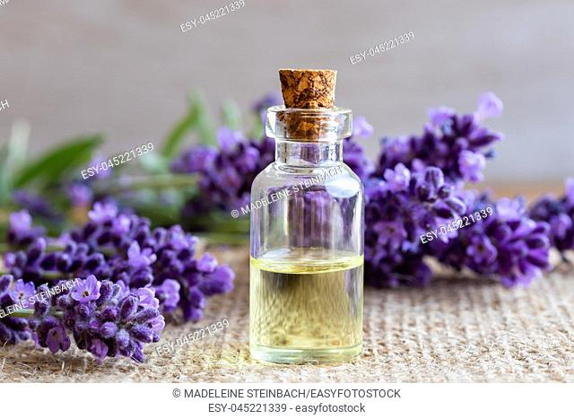 A bottle of essential oil with fresh blooming lavender twigs