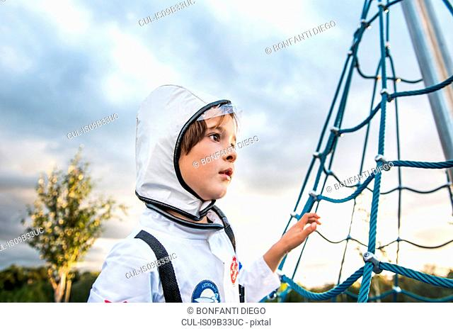 Portrait of boy in astronaut costume gazing by playground climbing frame