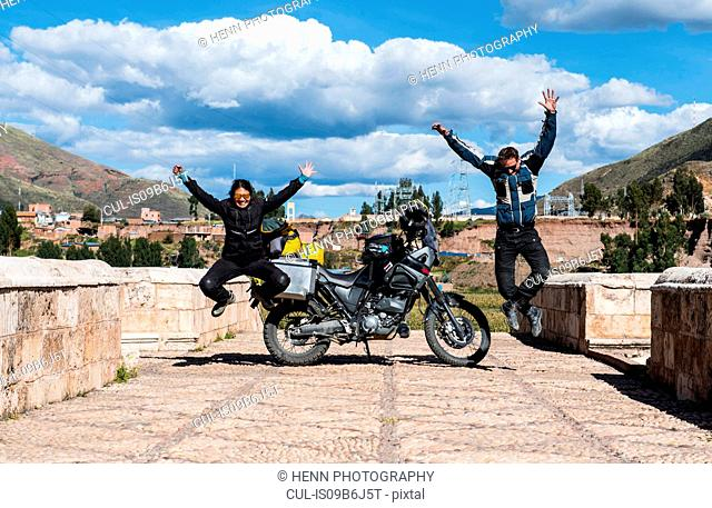 Motorcyclists celebrating on bridge over Urubamba River, Chocosillane Pucara, Cusco, Peru, South America