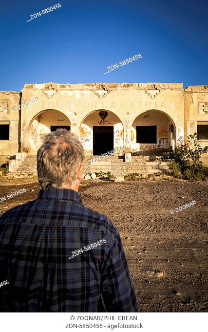 Man approaching old derelict building with Todo por La Patraia written above the arches. Old abandoned building in a leper sanatorium in Poris de Abona