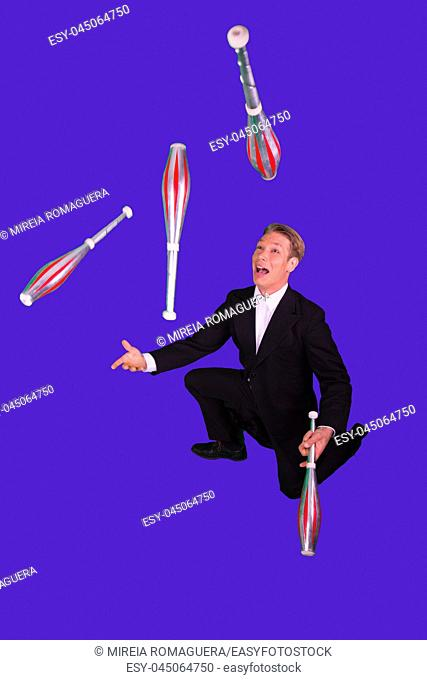 Elegant man juggling and struggling with four clubs on his knees