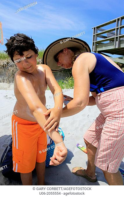 a senior woman applying sunscreen to her grandson at a beach