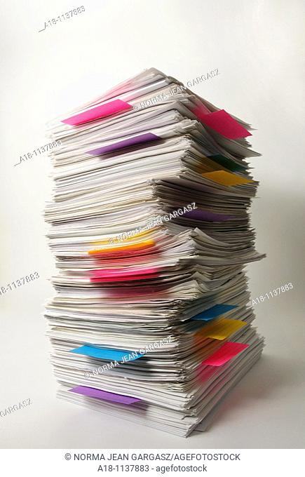 A stack of white sheets of paper with colored paper markers
