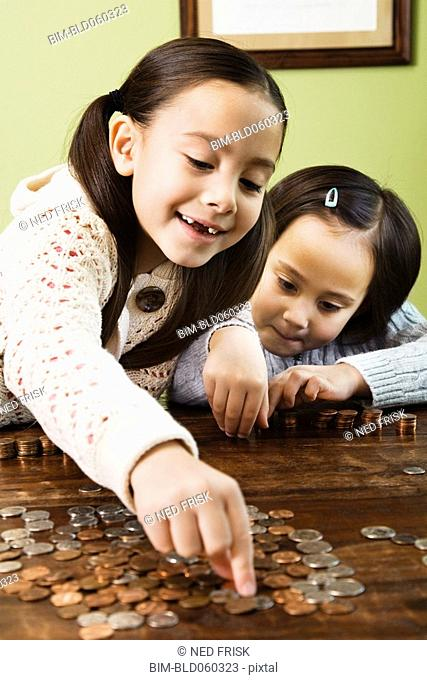 Asian sisters counting coins
