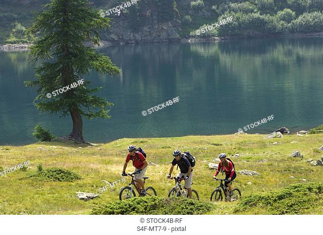 Three mountainbike riders driving along the waterside