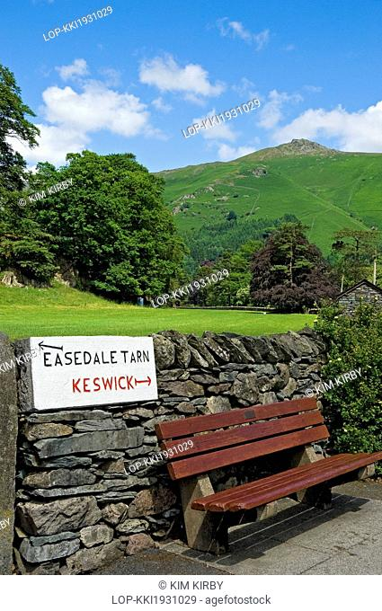England, Cumbria, Grasmere. A hand carved sign with directions to Easedale Tarn and Keswick on a stone wall