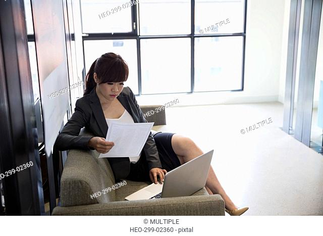 Businesswoman with paperwork using laptop on office sofa