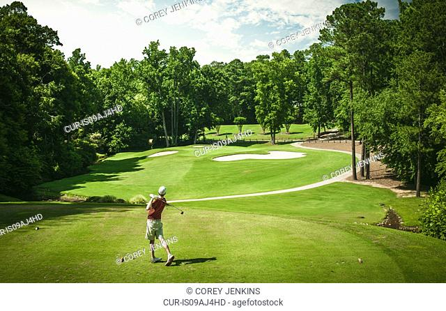 Elevated view of young male golfer teeing off on golf course, Apex, North Carolina, USA
