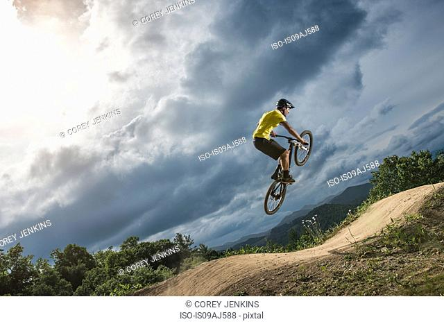 Young male mountain biker jumping mid air on rural pump track