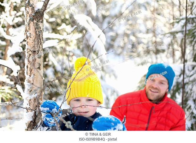 Man and son looking at tree twigs in snow covered forest