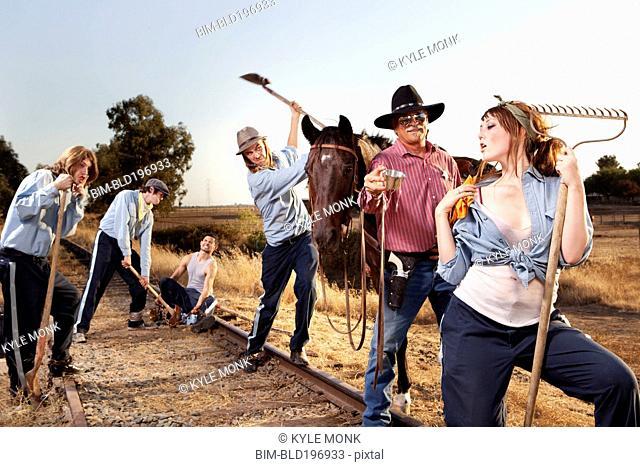 Sheriff watching criminals working on chain gang