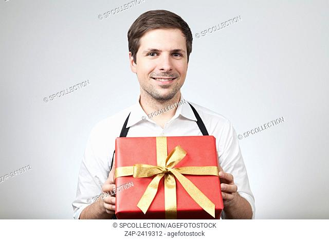 young man (shop assistant) with christmas present