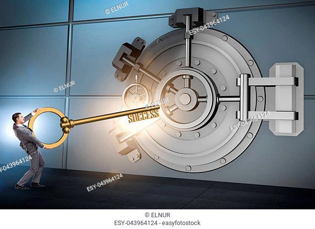 Businessman with key near bank vault door