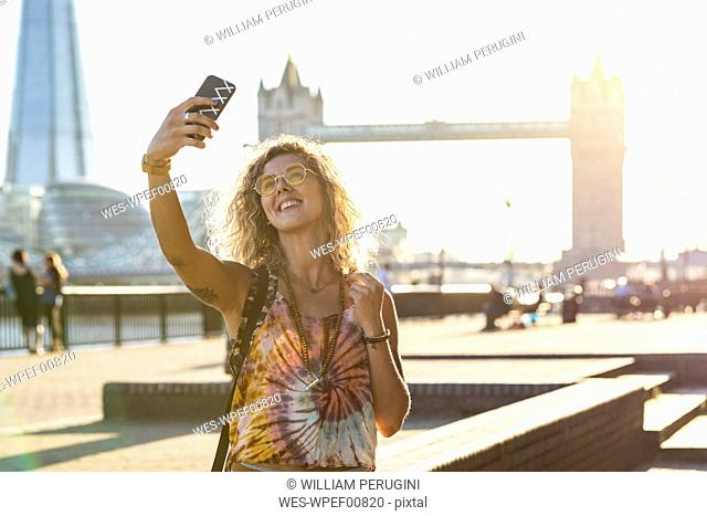 UK, London, smiling young woman taking a selfie with Tower Bridge in background