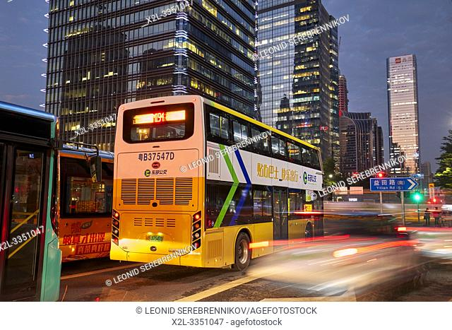 Electric city bus moving on street in Futian Central Business District at dusk. Shenzhen, Guangdong Province, China