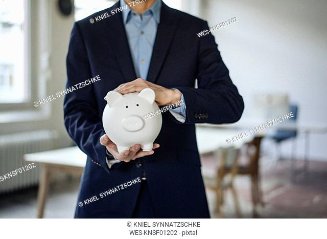 Close-up of businessman holding piggy bank