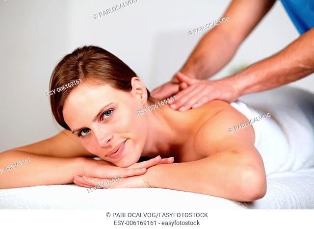 Close-up portrait of a pretty young blonde woman relaxing at a spa while receiving a massage at spa resort looking at you