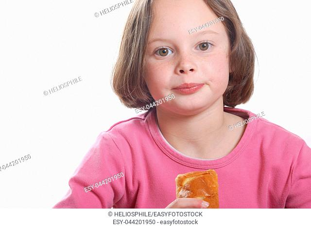 A young girl eating a bun