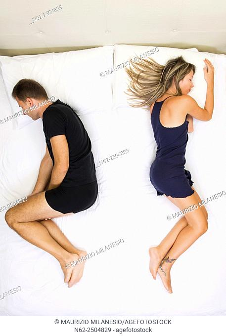 Unhappy couple sleeping far away from each other on bed top view