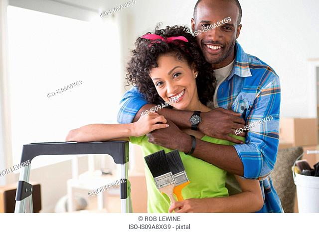 Portrait of mid adult couple, woman holding paintbrushes